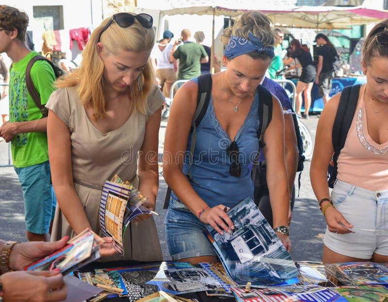 Lissabon Portugal - Augusti 05, 2017: Kvinnor rymmer fotona av Lissabon på marknaden royaltyfria bilder