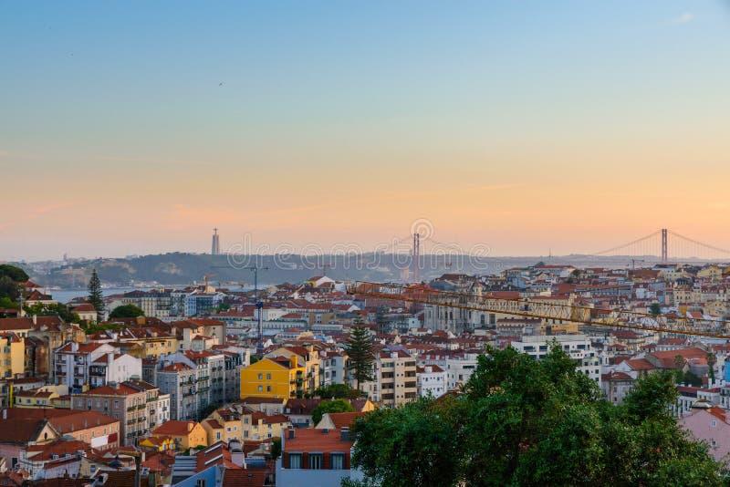 Lissabon, Portugal gammal stadhorisont med sikt på floden Tagus och bro på solnedgång arkivfoto