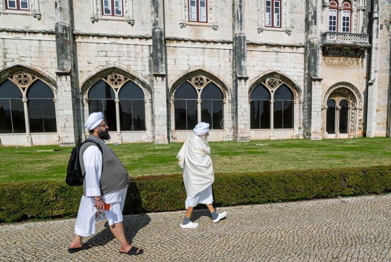 Lissabon Portugal Indiska turistmän i traditionell kläder som går ner gatan mot väggarna av slotten royaltyfri fotografi