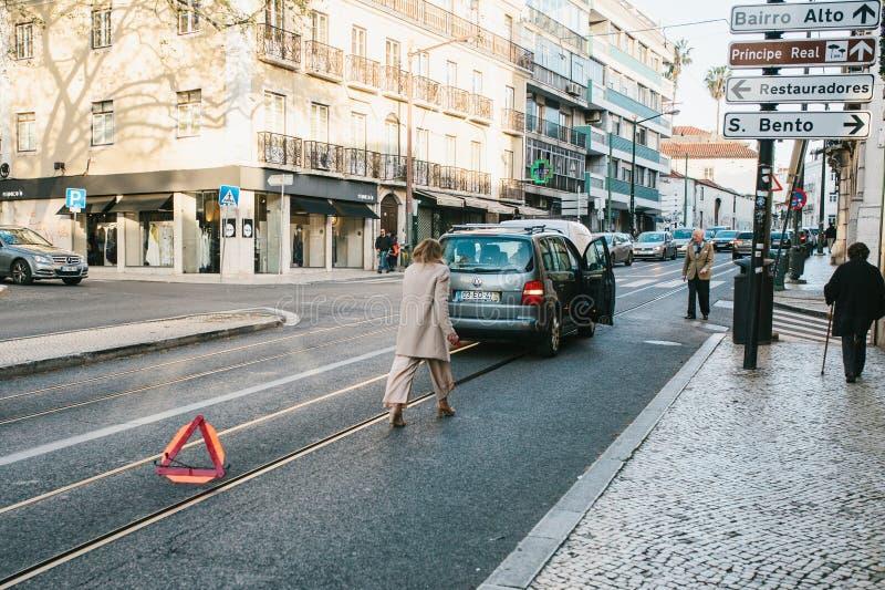 Lissabon Portugal 01 kan 2018: nödläget eller chauffören eller kvinnan sätter vägmärket Bilkostnader på nöd- signal eller trafik  royaltyfria bilder