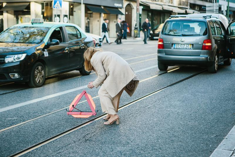 Lissabon Portugal 01 kan 2018: nödläget eller chauffören eller kvinnan sätter vägmärket Bilkostnader på nöd- signal eller trafik  royaltyfri foto