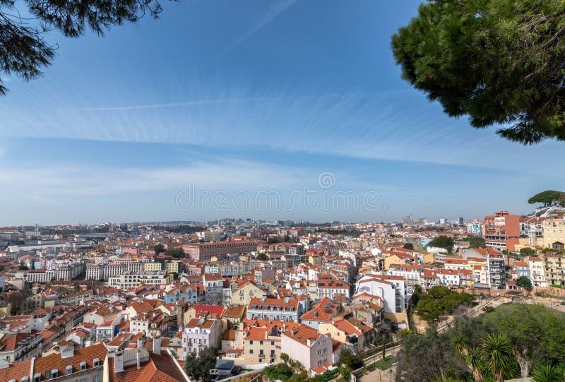 LISSABON PORTUGAL - Maj 2019 Sikt av staden från observationsdäcket som inramas av filialer mot den blåa himlen med moln på a royaltyfria foton