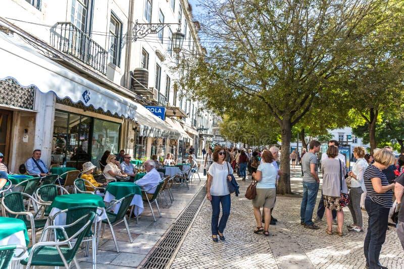 Lissabon, Portugal - Maj 9th 2018 - turister och lokaler som i city går i en traditionell bana i Lissabon, restauranger och träd  royaltyfri fotografi