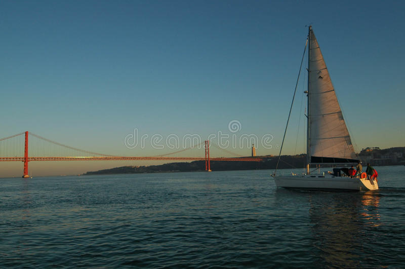 Lissabon-Segelboot und 25 De Abril Bridge, der Tajo stockfotos