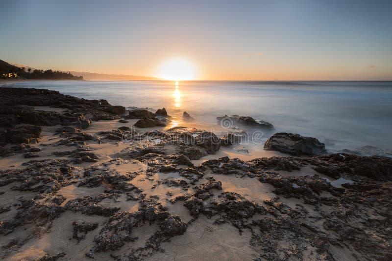 Lissez les vagues roulant dans au-dessus du corail sur la plage de coucher du soleil, Hawaï photo libre de droits