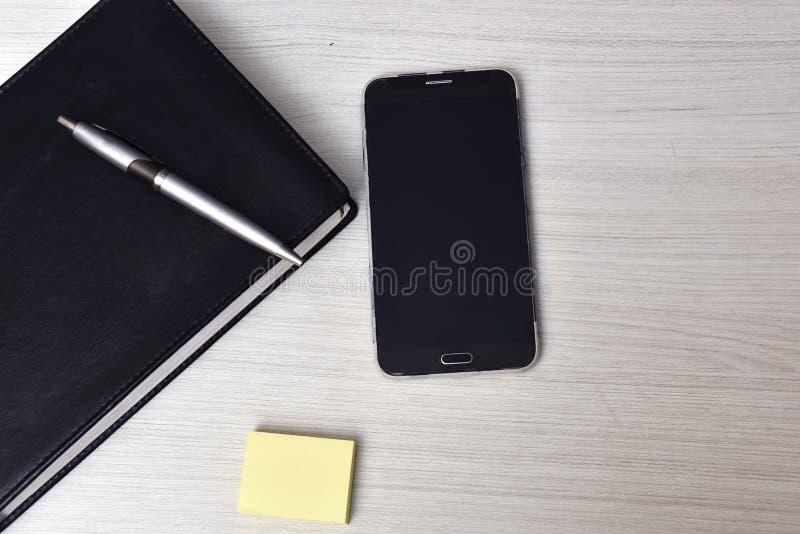 Listín de teléfonos con la pluma en el top y el teléfono móvil en la tabla imagen de archivo