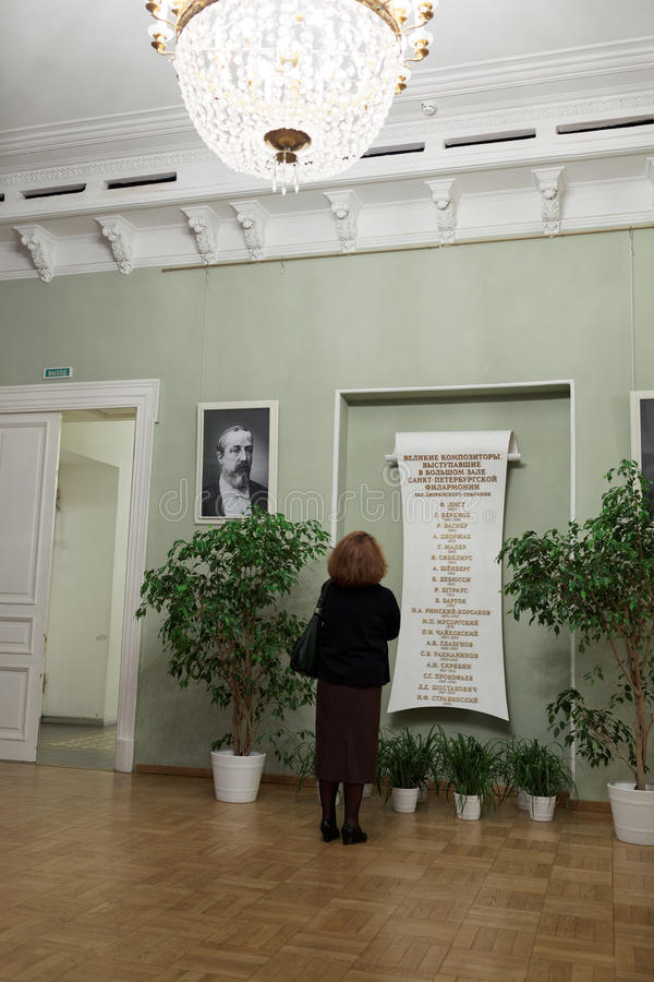 List of great composers performing in the St. Petersburg Great Philharmonic Hall. St. Petersburg, Russia - December 7, 2015: Woman reading the list of great royalty free stock image