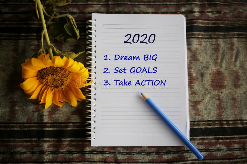 2020 new year resolutions list. Dream big. Set goals. Take action. With text on notebook paper, yellow flower and pen arrangement. stock photo