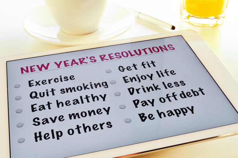 List of new years resolutions. A list of new years resolutions in a tablet, on a table with a cup of coffee and a glass with orange juice royalty free stock photos