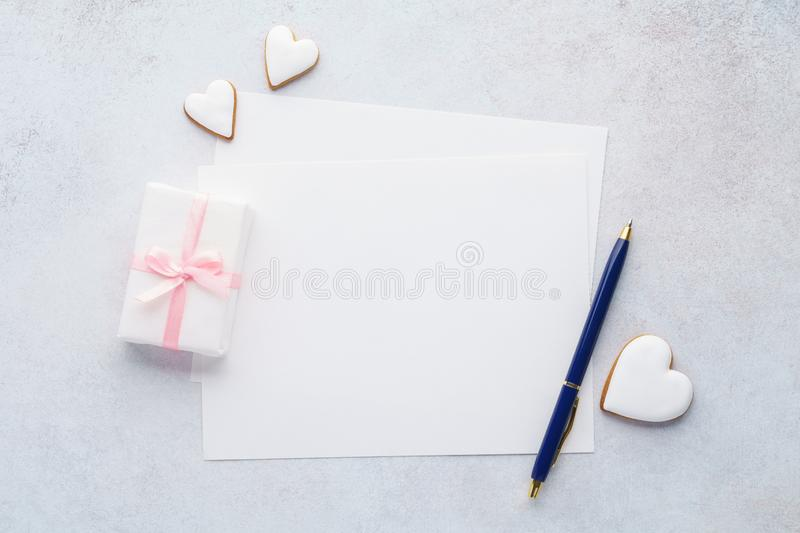 List of paper, gift box, heart shaped cookies and a pen. stock image
