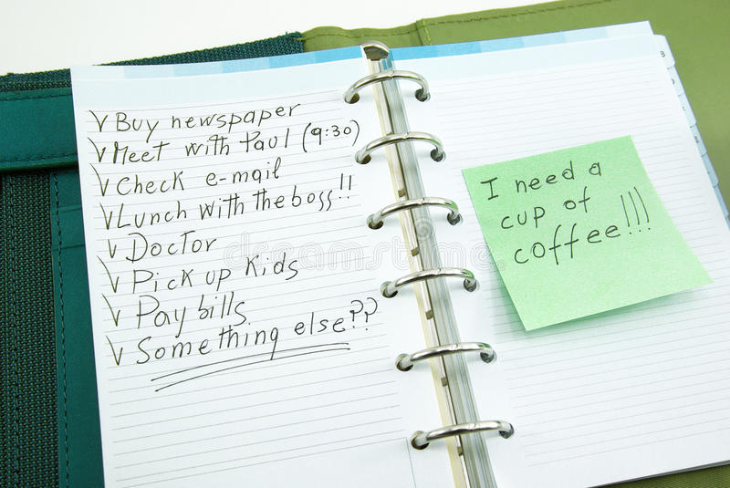 A list of things to do with post it. A list of things to do on notepad with post it, i need a cup of coffee stock photo