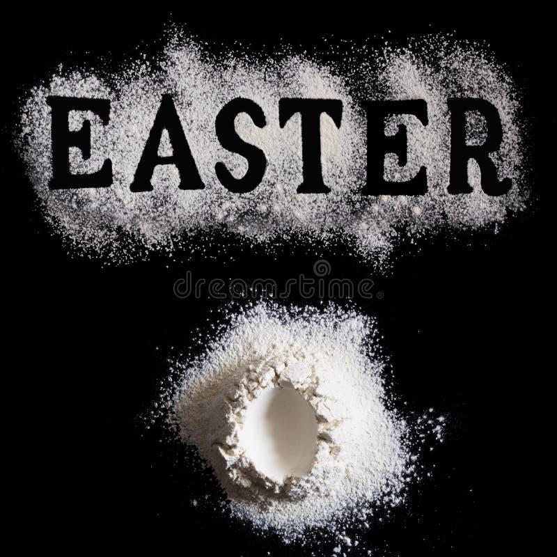 List wielkanoc robić z sieved mąką i Handrful mąka z z jajeczną kształt dziurą w centrum na czarnym tle, wielkanoc fotografia royalty free