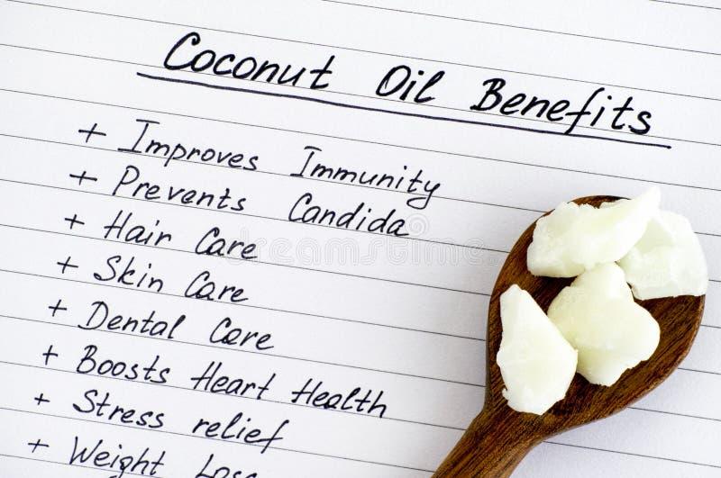 A lista de óleo de coco beneficia-se com a colher de madeira com óleo de coco imagens de stock