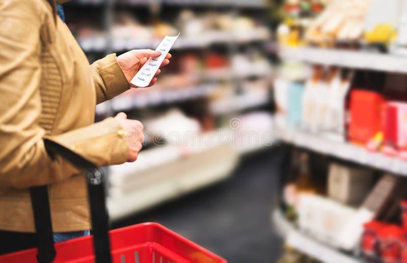 Lista de compra da leitura no supermercado Cliente fêmea fotografia de stock royalty free