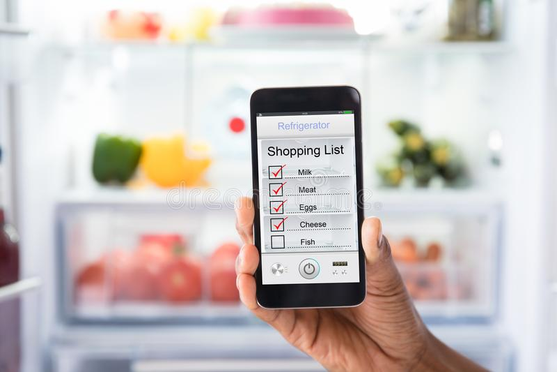 Lista de compra humana da marcação da mão no telefone celular fotos de stock royalty free