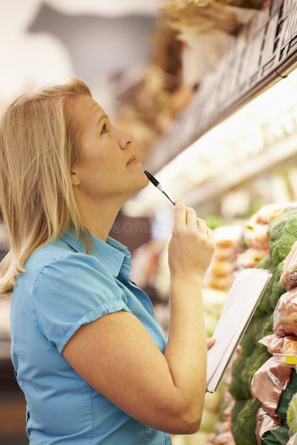 Lista de compras de la lectura de la mujer en supermercado imagenes de archivo