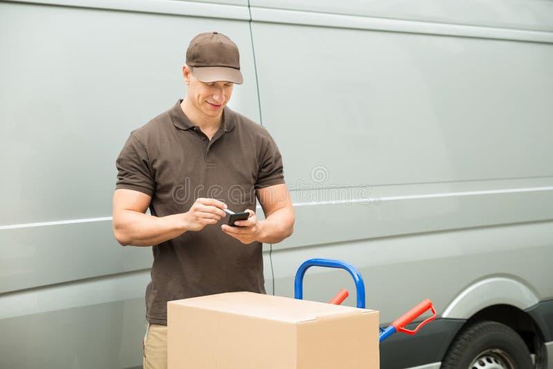 Lista de comprobación del hombre de entrega en el teléfono móvil fotografía de archivo libre de regalías