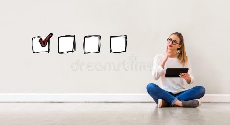 Lista de control con la mujer que usa una tableta imagen de archivo