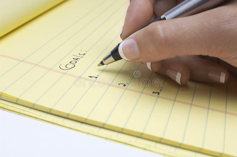Lista de la escritura de la mano de metas en la libreta foto de archivo libre de regalías