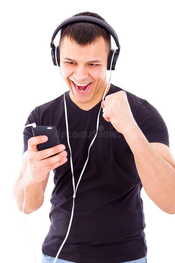 Lista de músicas de escuta do homem em fones de ouvido vestindo do telefone celular imagem de stock