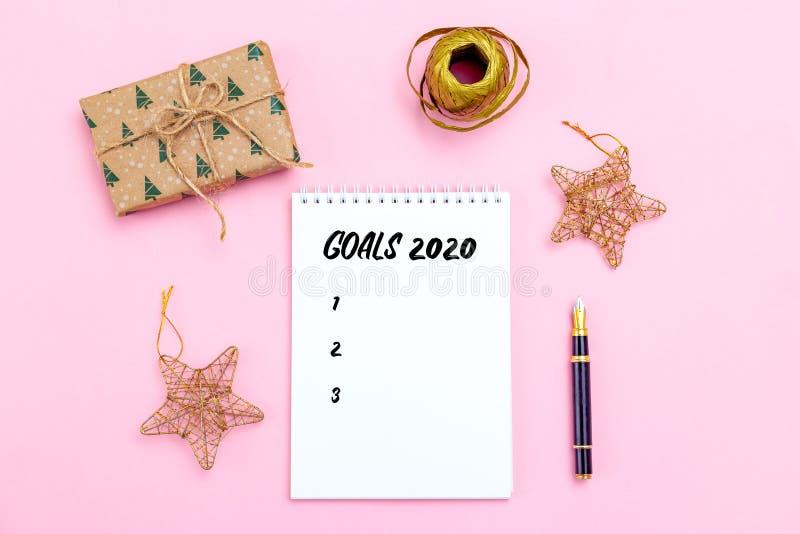 Lista de objetivos Bloc de notas con bolígrafos y accesorios dorados de Navidad sobre fondo rosa Hora de Navidad imagenes de archivo