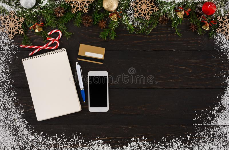 Lista de objetivos pretendidos do Natal, telefone, cartão de crédito, pena e bastões de doces no fundo de madeira rústico da tabe fotografia de stock