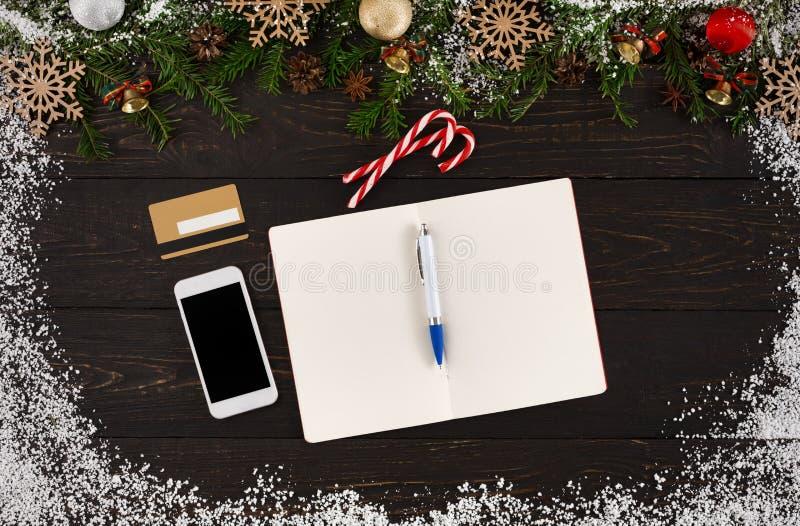 Lista de objetivos pretendidos do Natal, telefone, cartão de crédito, pena e bastões de doces no fundo de madeira rústico da tabe imagem de stock