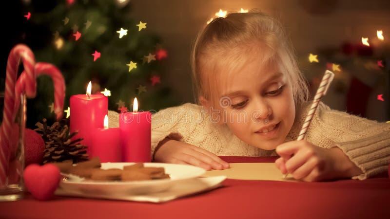 Lista de objetivos que compone de la niña antes de los días de fiesta de la Navidad, para presentes que esperan fotografía de archivo libre de regalías