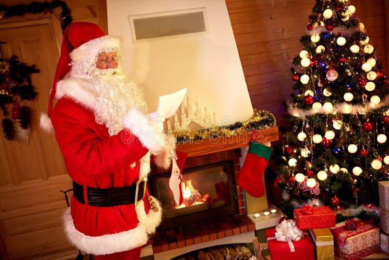 Lista de presente da leitura de Santa Claus para o Natal foto de stock