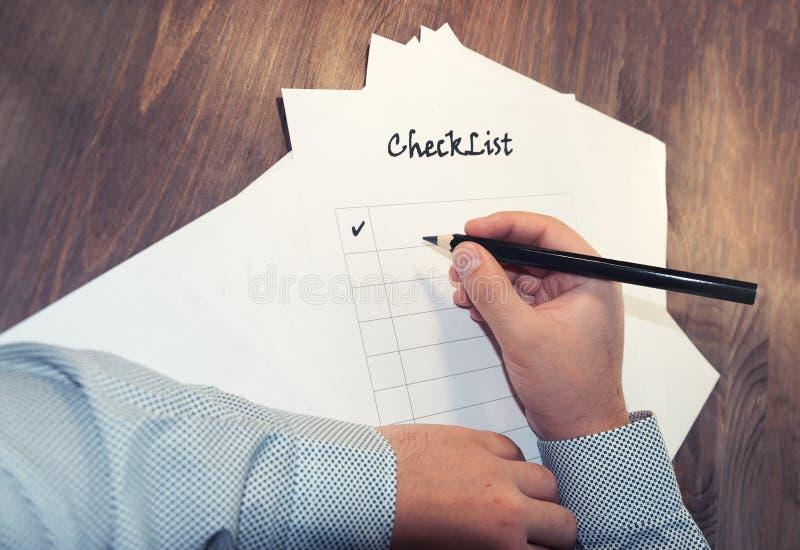 lista de verificação vazia na folha de papel da tabela A de madeira na frente de um homem com as palavras: Lista de verificação P imagem de stock