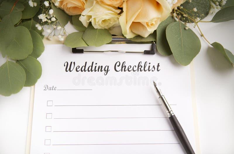 Lista di controllo di pianificazione di nozze con spazio e le rose fotografie stock