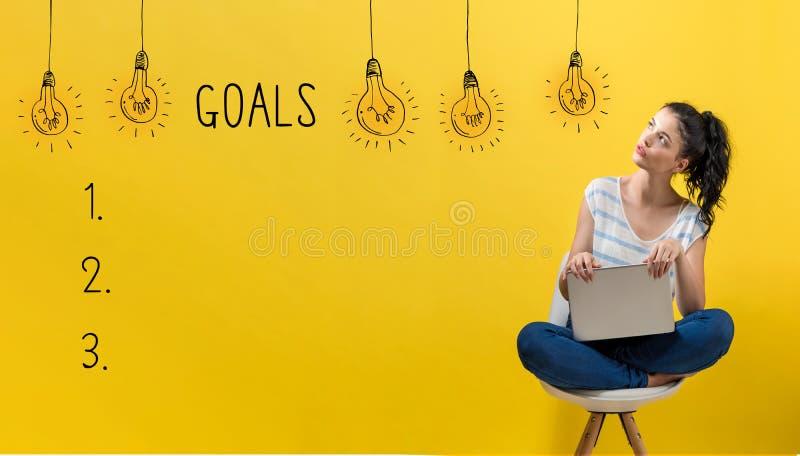 Lista do objetivo com a mulher que usa um portátil fotos de stock royalty free
