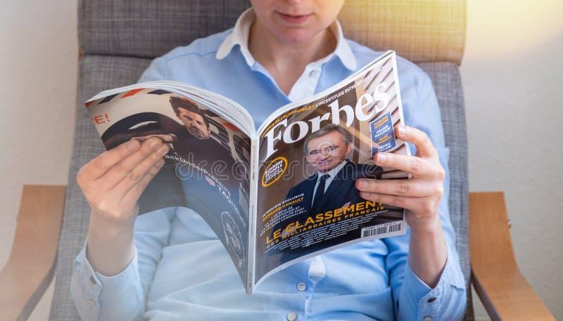 Lista dos multimilionário de Forbes France da leitura da mulher fotos de stock