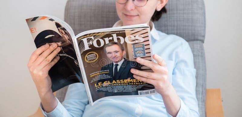 Lista dos multimilionário de Forbes France da leitura da mulher imagens de stock