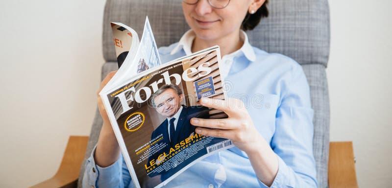 Lista dos multimilionário de Forbes France da leitura da mulher foto de stock