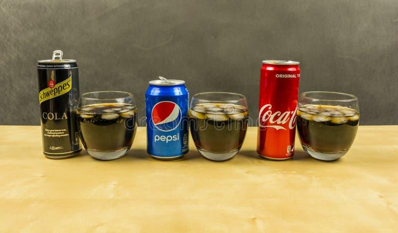 Lista en coladrink från producenter: Pepsi, coca - cola och Schweppes Cola som framläggas i exponeringsglas med iskuber arkivfoton