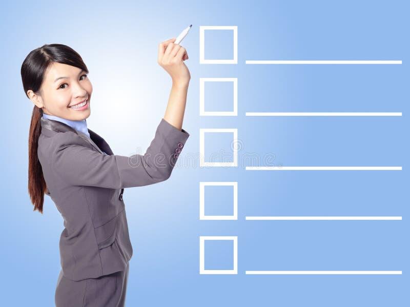 Listar den fyllnads- kontrollen för affärskvinnan royaltyfri bild