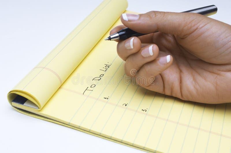 Liste d'écriture de main de tâches de faire sur le bloc-notes photographie stock libre de droits