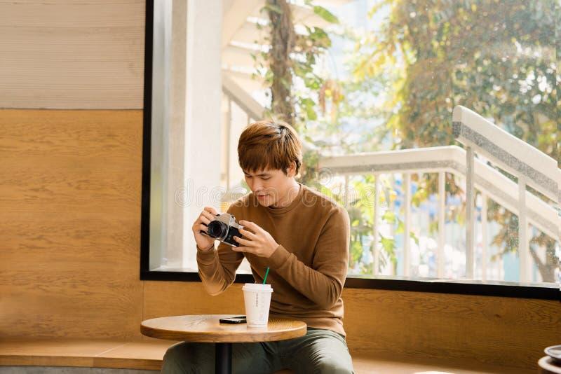 Liste de contrôle professionnelle songeuse de lecture de photographe se reposant avec la caméra de stylo et de cru à la table  photographie stock