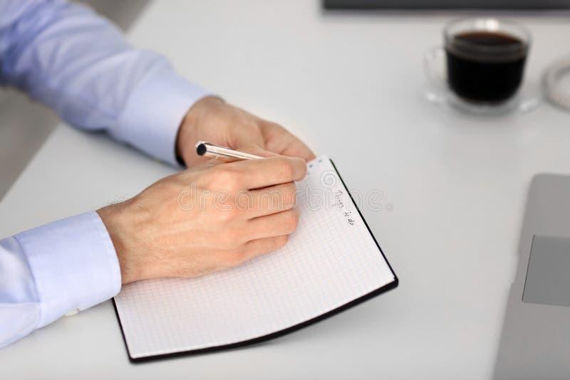 Liste de remue-ménage d'écriture d'homme d'affaires à la table dans le bureau photos stock