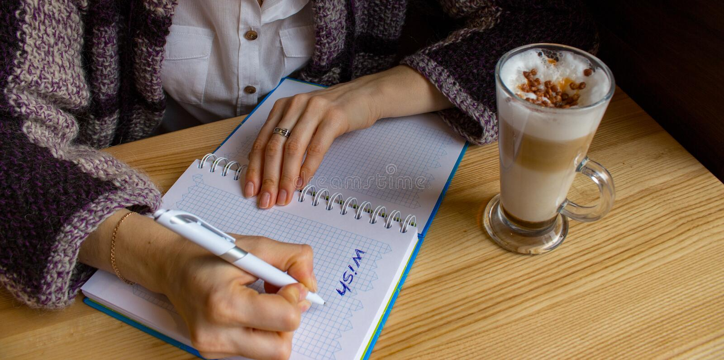Liste de souhaits d'écriture de jeune femme dans le carnet ouvert en café Planification de nouvelle année Rêves et concept de but images stock