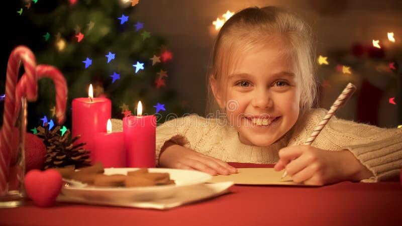 Liste de sourire d'écriture de fille de présents pour la famille avant des vacances, réveillon de Noël photographie stock