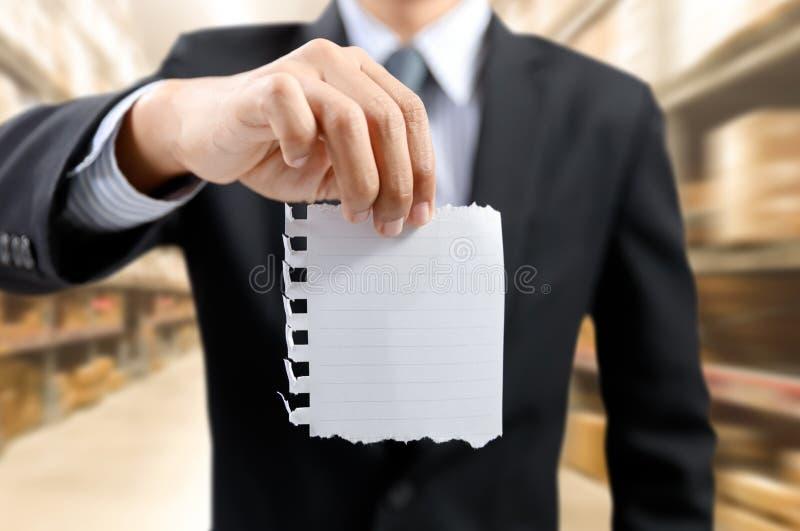 Liste des tâches d'exposition d'homme d'affaires sur le bloc-notes avec le fond d'entrepôt image libre de droits