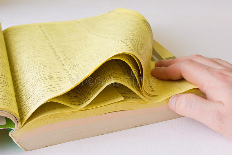 Listed yellow pages. Man hand stock photography