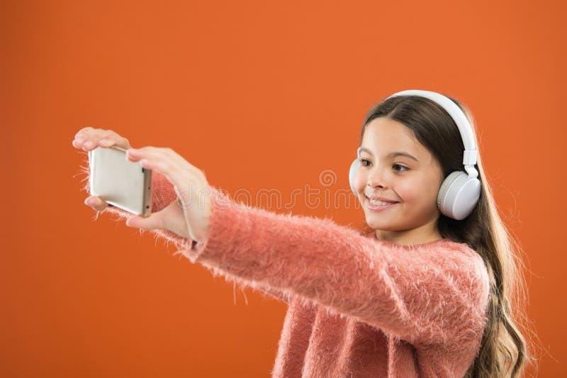 Listen for free. Mobile application for teens. Girl child listen music modern headphones and smartphone taking selfie stock photography