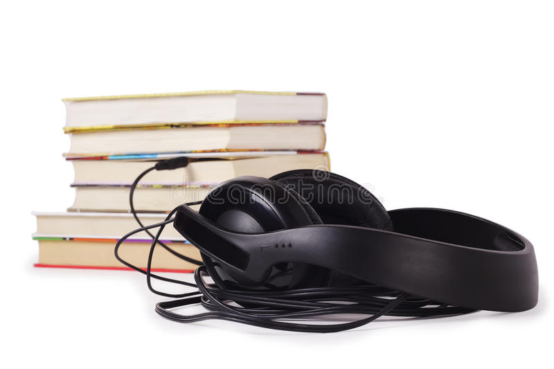 Listen to books. Headphones are connected to a stack of different books royalty free stock photo