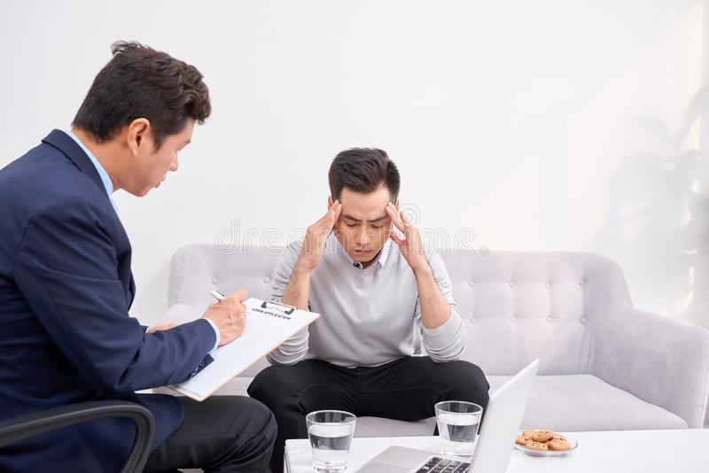 Listen to me. Asian man wrinkling forehead while looking at his therapist. Listen to me. Asian men wrinkling forehead while looking at his therapist stock photo