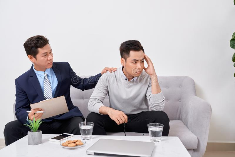 Listen to me. Asian man wrinkling forehead while looking at his therapist. Listen to me. Asian men wrinkling forehead while looking at his therapist stock image