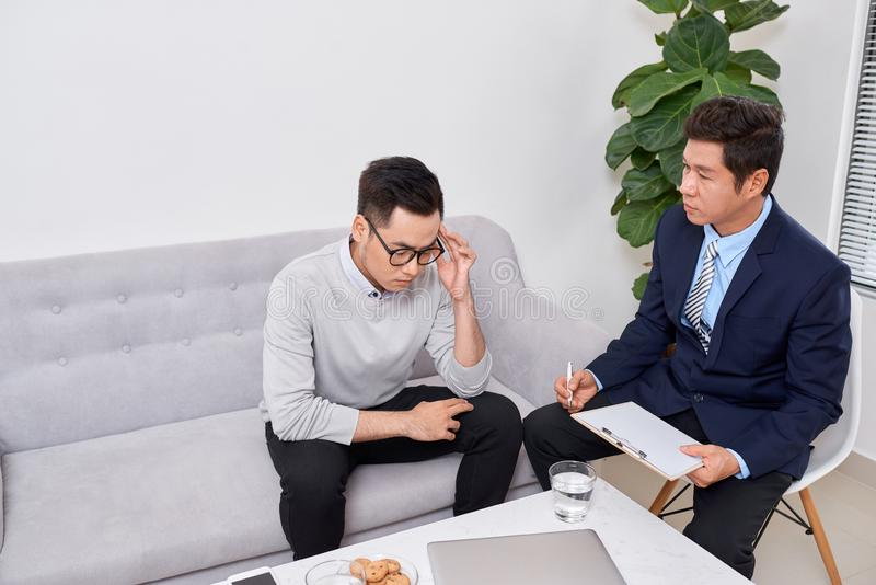 Listen to me. Asian man wrinkling forehead while looking at his therapist. Listen to me. Asian men wrinkling forehead while looking at his therapist stock images