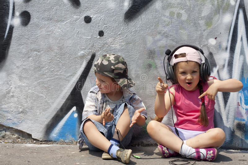 Listen to music. Kids listen to music abstract concept against graffiti wall in the city stock images